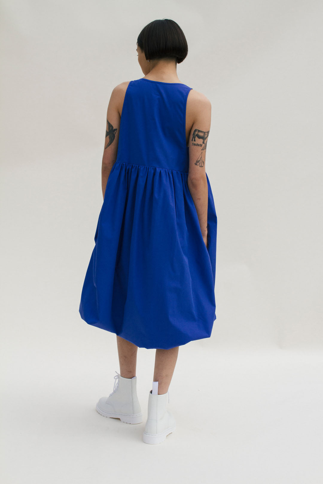 bright blue oversized bubble hem sleeveless dress made in cotton poplin, square neckline geometric-pieced bodice, side pockets and gathered empire waist, falls just below the knee, 100% cotton, made in NYC and Seattle, model on grey background in blue dress with white dr. marten boots