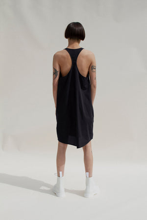 Scoop neck cocoon shaped racerback effortless dress, knee length made of crisp black cotton poplin. Dress has a shirttail hem. Model has short straight black hair, tatoos on her arms, and hite dr. marten boots. The background is grey with angular shadows, lots of sunlight.