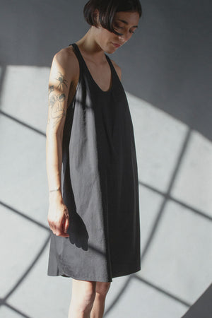 Scoop neck cocoon shaped effortless dress, knee length made of crisp black cotton poplin. Model has short straight black hair, and tatoos on her arms. The background is grey with angular box shadows, high contrast between the shadows and grey. Her arms are resting at her side and she is looking down, hair kinda falling in her face.