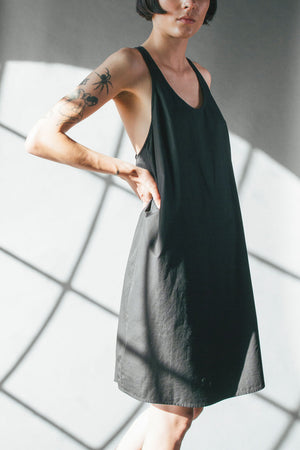 Scoop neck cocoon shaped effortless dress, knee length made of crisp black cotton poplin. Model has short straight black hair, and tatoos on her arms. The background is grey with angular box shadows, high contrast between the shadows and grey. She has her hands on her hips, elbows pointing out.