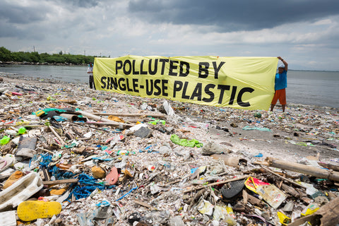Huge heaps of plastics washed onto the coastline. Two people hold up a large banner that states: polluted by single-use plastic