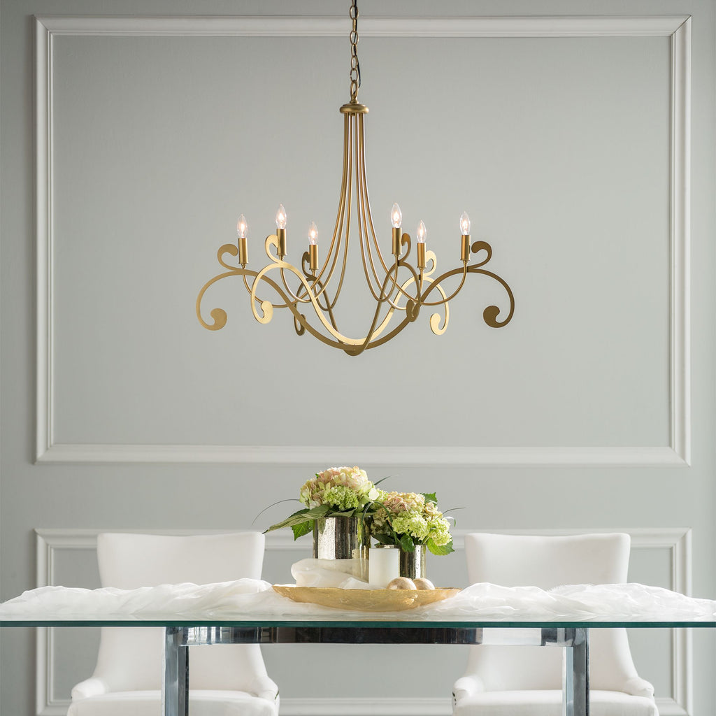 Bella 6 Arm Chandelier in gold finish hanging over dining table,  Synchronicity by Hubbardton Forge