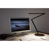 Metallic Black Z-bar LED desk lamp from Koncept lighting standing on desk lighting keyboard