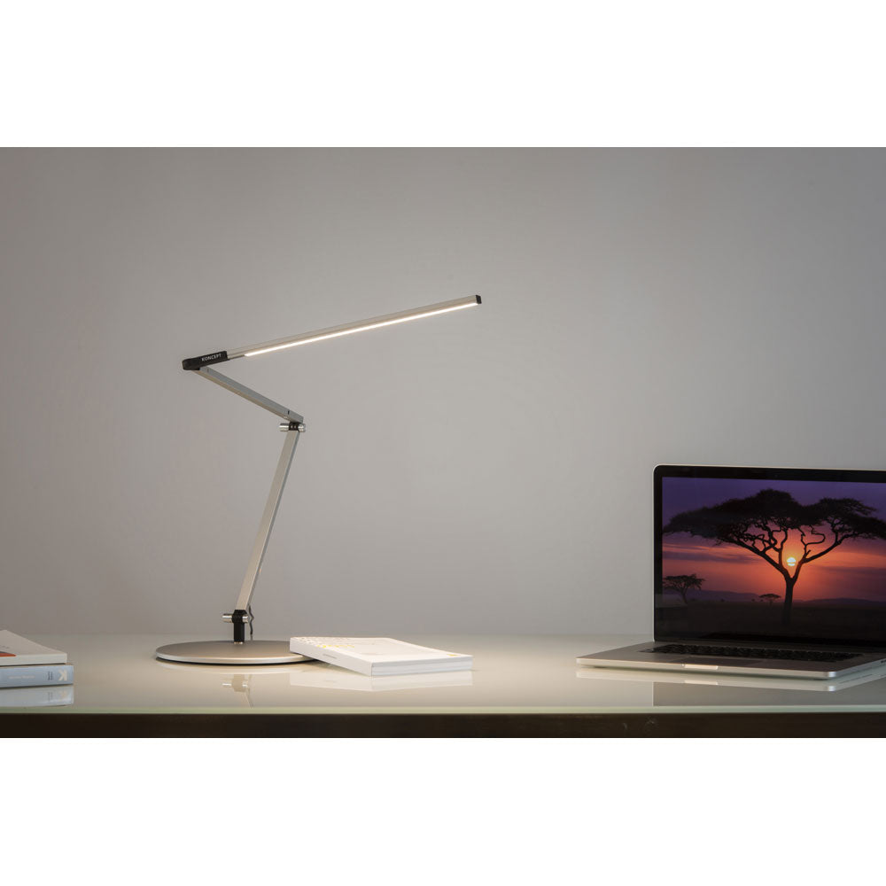 z-bar slim led desk lamp by koncept lighting on a white desk lighting a laptop