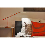 ORANGE EQUO DESK LAMP USED AS READING LAMP AT BEDSIDE