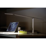 SILVER EQUO DESK LAMP LIGHTING A LAPTOP ON A DESK