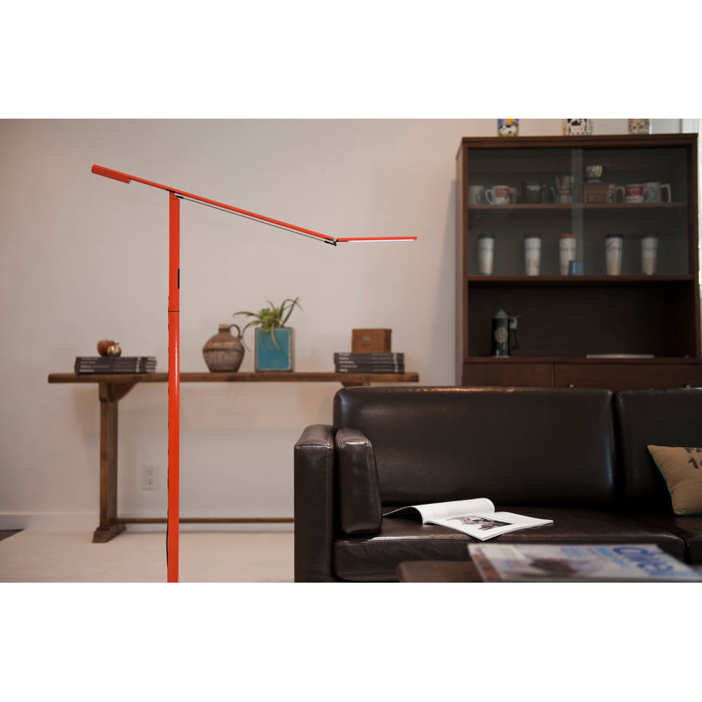 ORANGE EQUO DESK LAMP NEXT TO LEATHER ARM CHAIR