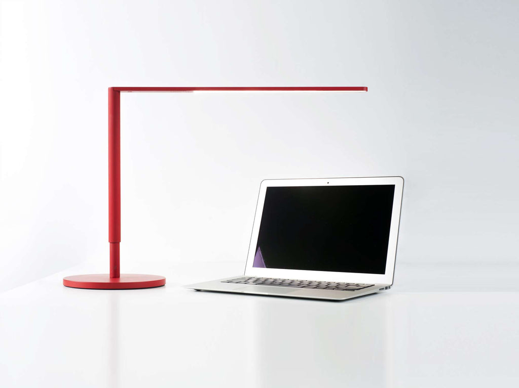 Matte red Lady 7 LED desk lamp on table over laptop