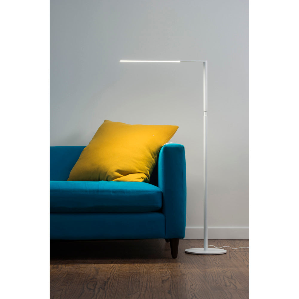 Lady 7 LED floor lamp in matte white next to blue sofa with yellow pillow