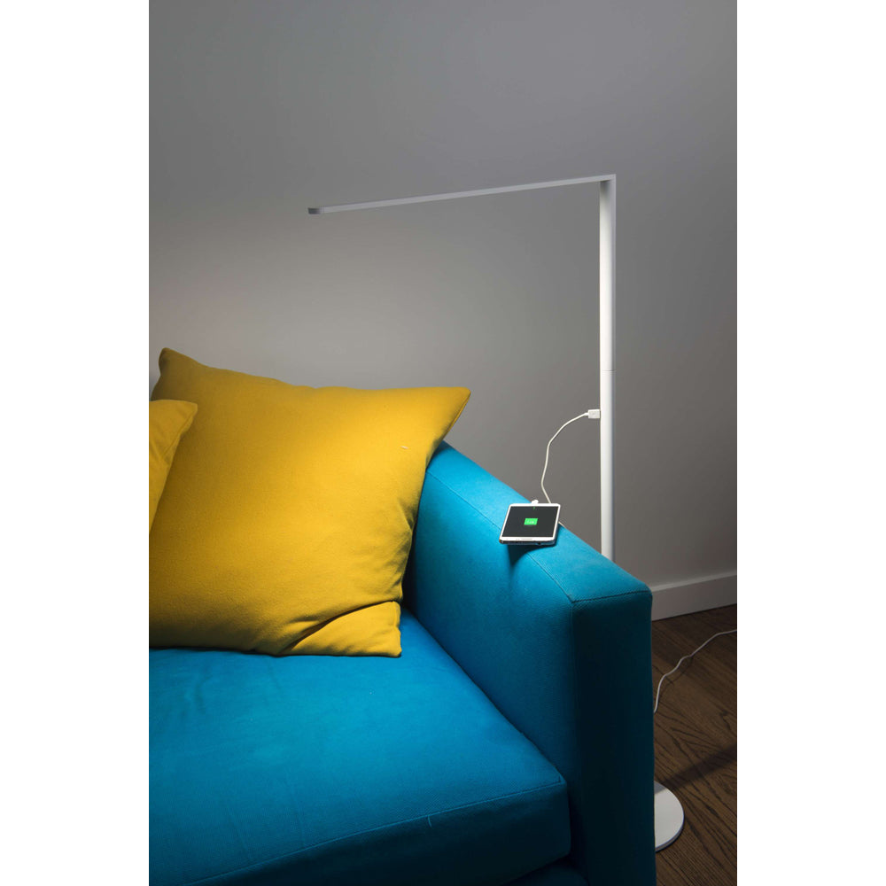 Matte white Lady 7 Floor lamp next to blue sofa with yellow pillow charging cell phone