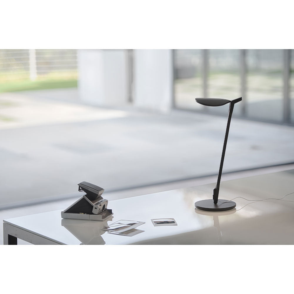 Splitty LED desk lamp from koncept lighitng in matte black on a desk lighting polaroid pictures