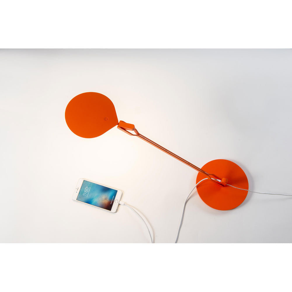 Splitty desk lamp in matte orange charging a mobile phone, Koncept lighting