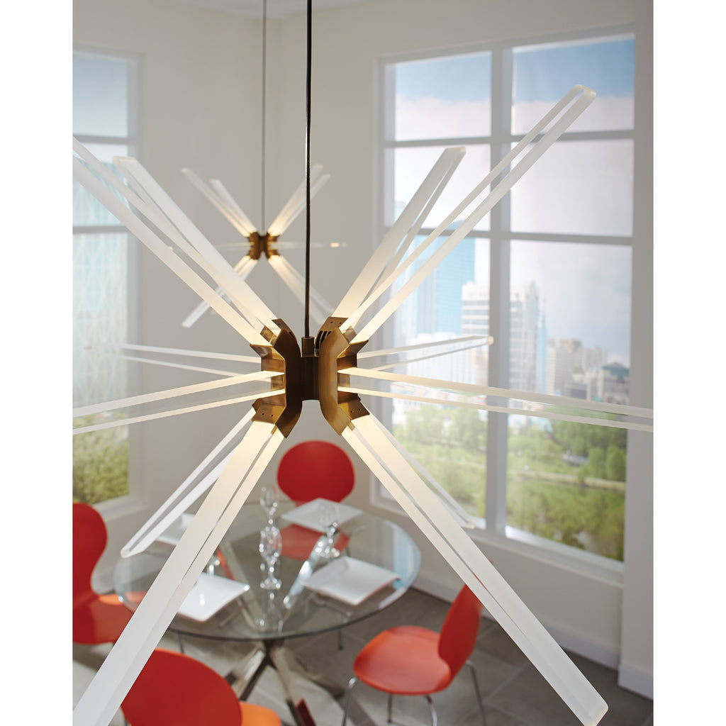 Photon pendant in aged brass hanging over glass dining table