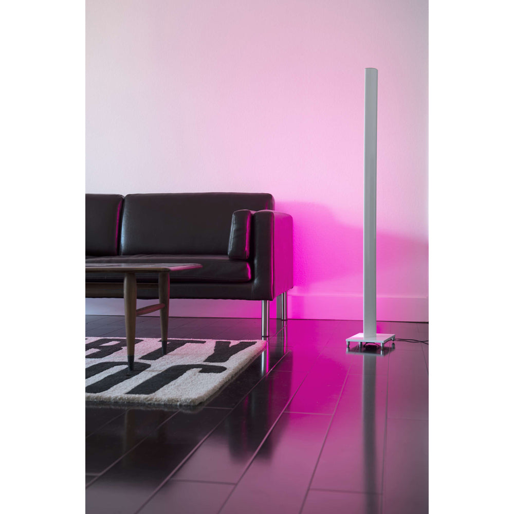 Tono LED floor lamp next to a black sofa washing the wall in pink light