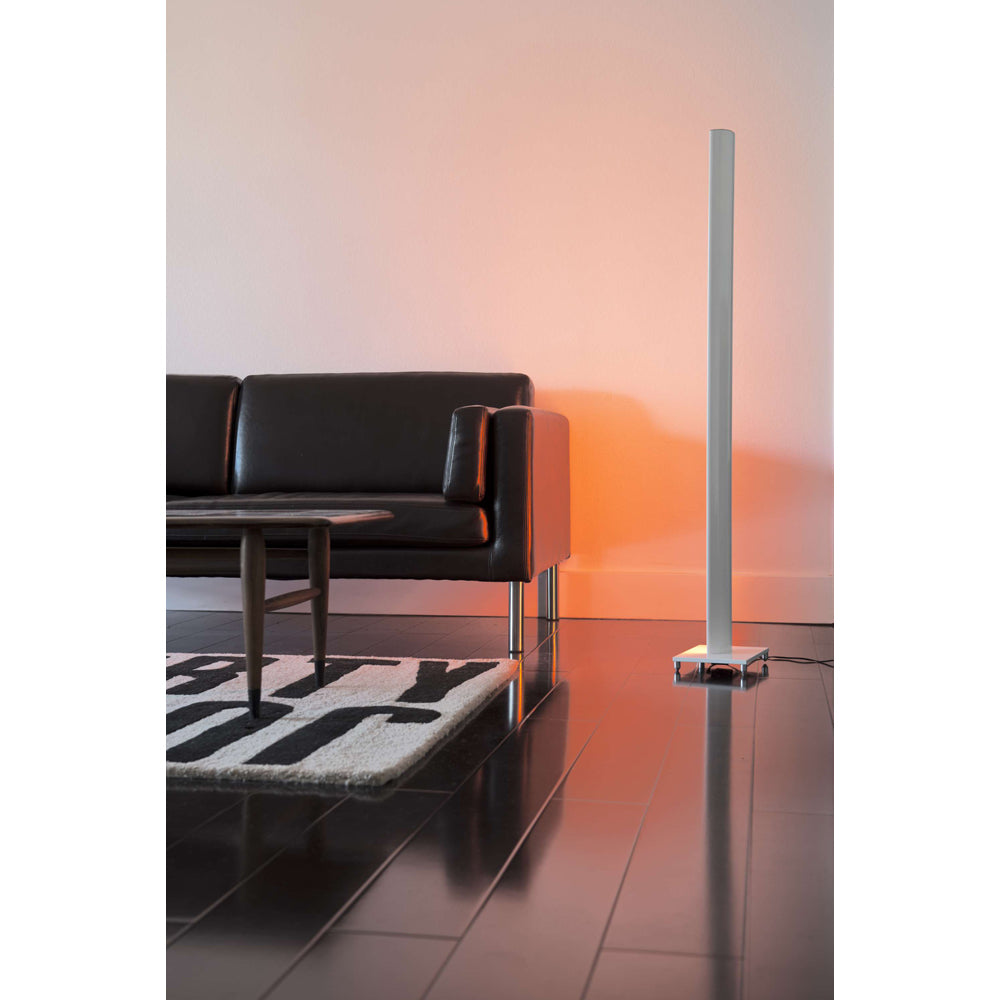 Tono LED floor lamp next to a black sofa washing the wall in orange light