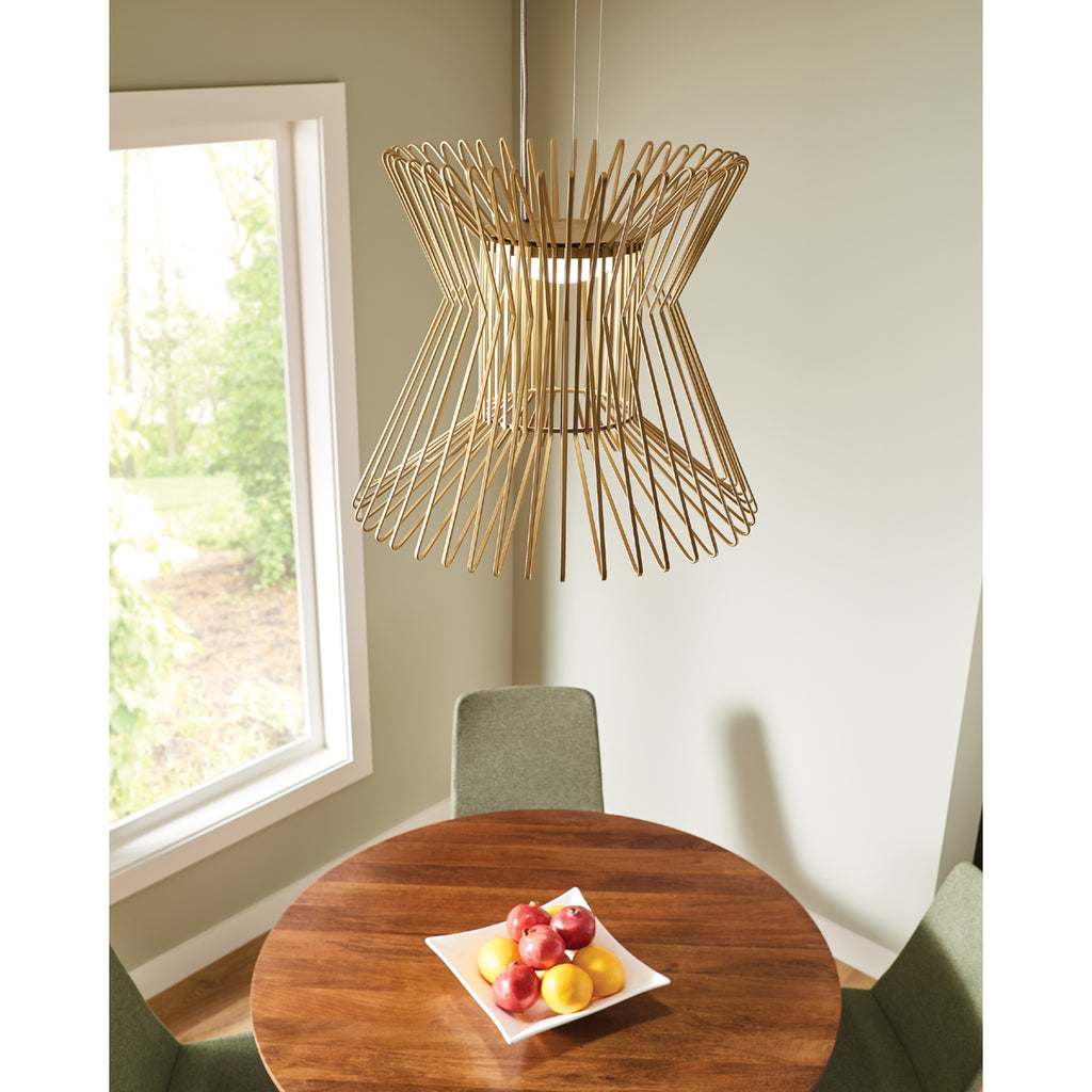syrma grande pendant in satin gold hanging over round wood dining table
