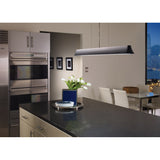 zhane linear pendant in satin nickel hanging over black granite kitchen island