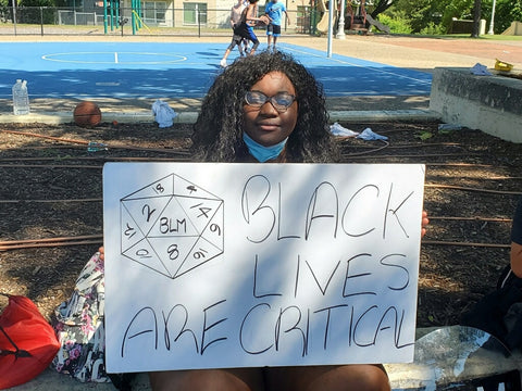 A young black person sits holding a sign at a protest with a D20 drawn on it and the initials BLM on the 20 face. Their sign says Black Lives are Critical