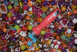 A pink handled ice cream scoop is laying on hundreds of different dice in different designs.