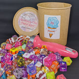 Brown Kraft cardboard ice cream tub with a white sticker stands behind a pink handled ice cream scoop and about 100 dice of mixed designs.