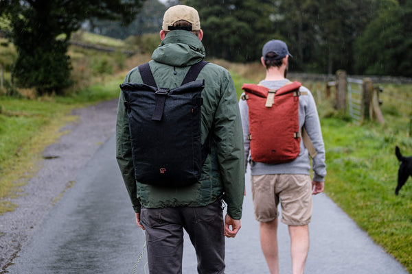 Two men wearing bear waxed canvas waterproof backpacks with cobra buckles that have been made in england.