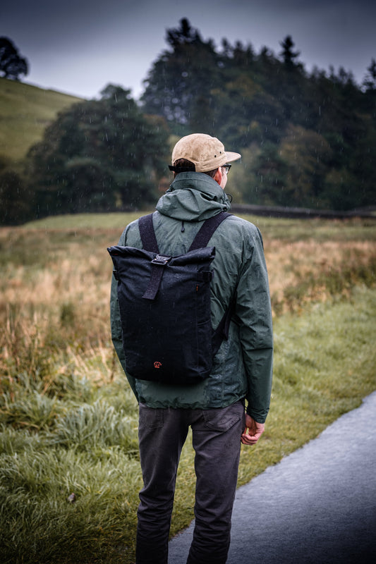 A man looking at the forest wearing a Bear waxed canvas bag with a cobra buckle