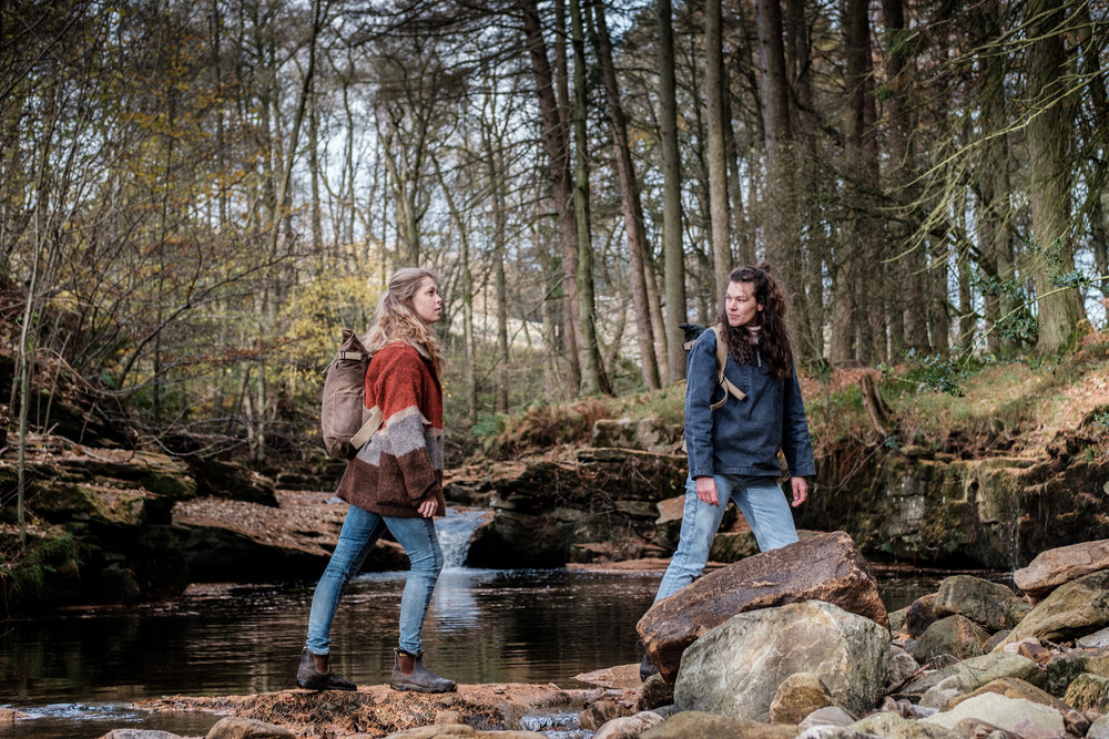 Bear waterproof waxed canvas bags that have been made in england being worn in the outdoors by two women.