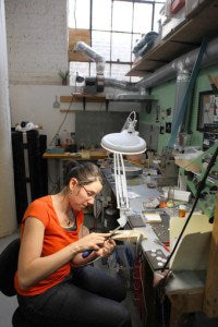 Jewelry artist in studio at the bench working