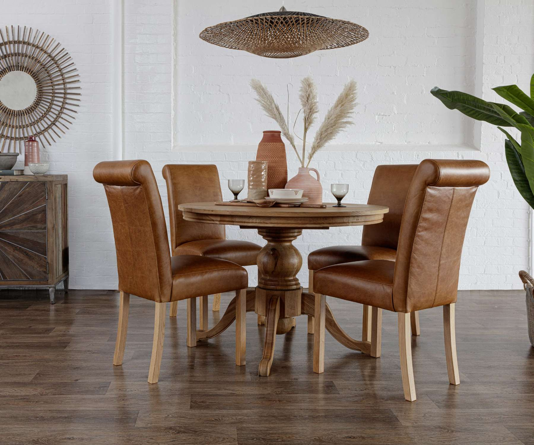oak round dining table with brown faux leather chairs