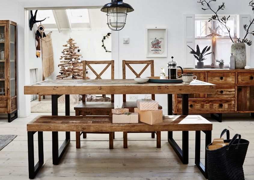 Industrial reclaimed wood dining table with matching wooden bench and Christmas tree in background