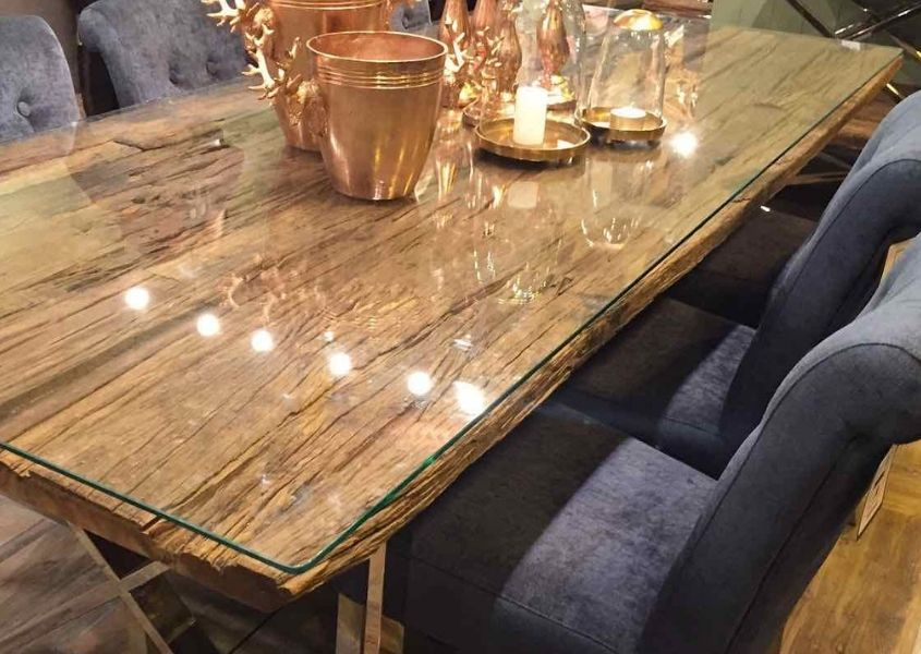 Close up of reclaimed wood dining table with glass top and blue fabric dining chairs