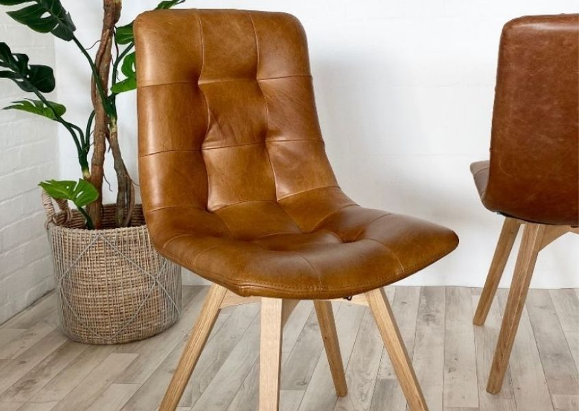 Tan leather dining chair with wooden legs and floor plant in background