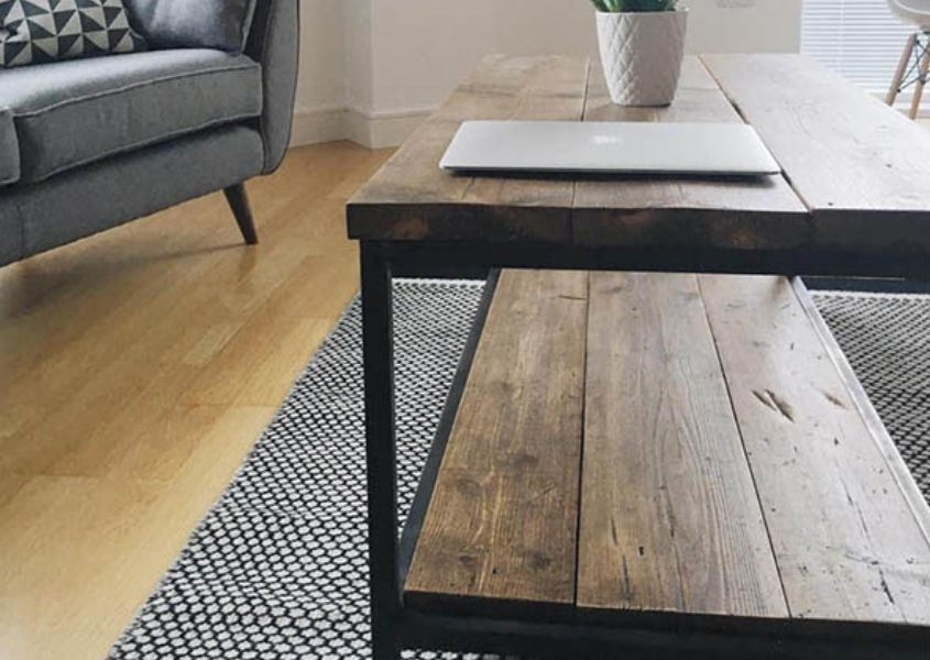 Industrial reclaimed wood coffee table on grey rug with sofa in background