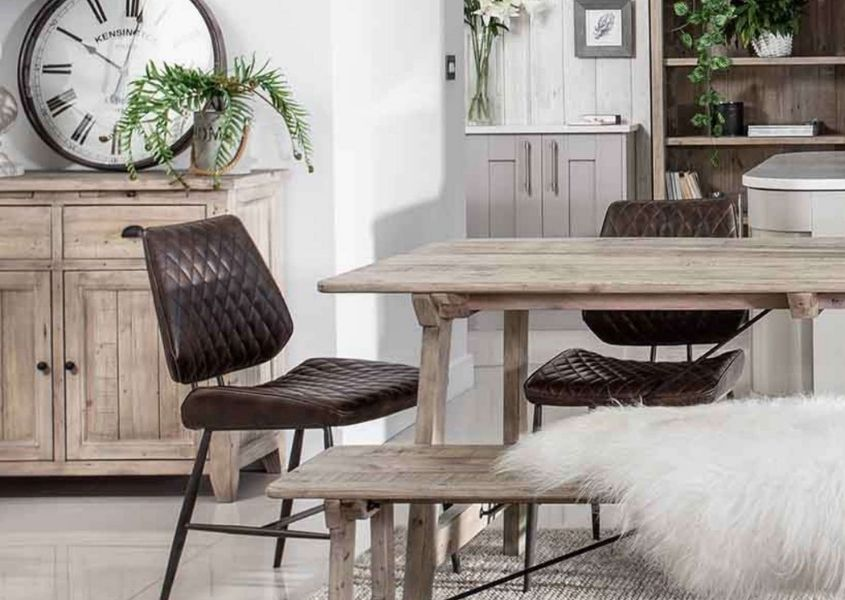 Dining room with pale reclaimed wood dining table and wooden bench with brown faux leather dining chair and rustic sideboard