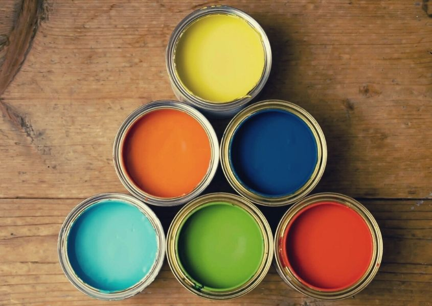 Six small paint pots with different coloured paints inside on wooden table