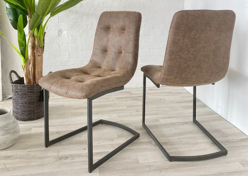 Two light brown faux leather dining chairs with black metal u-shaped legs and large green plant in background