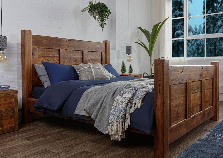 Reclaimed wood bed with dark blue bed covers and hanging green plants