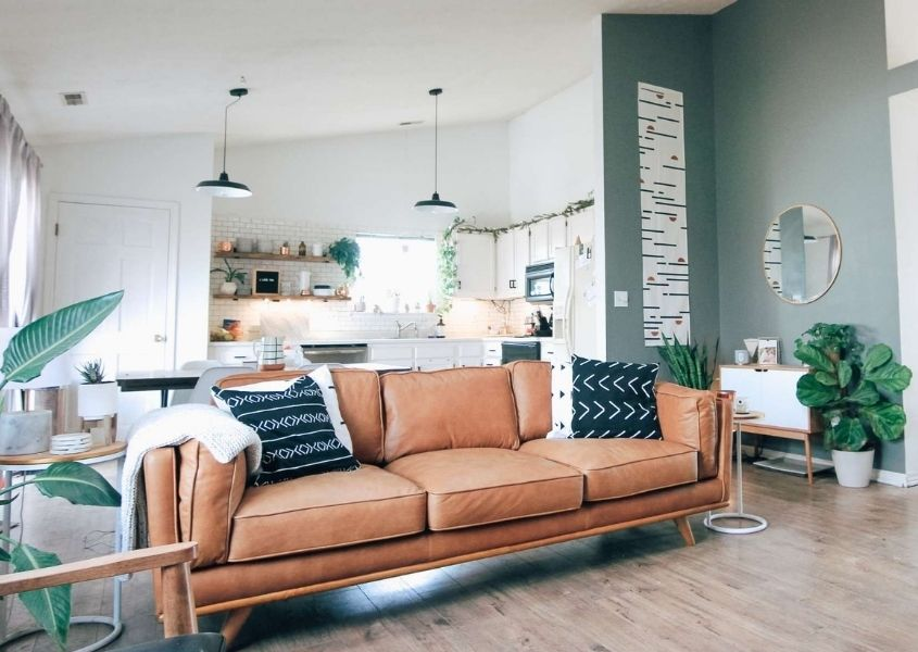 Brown leather sofa in open plan living room and white kitchen in background