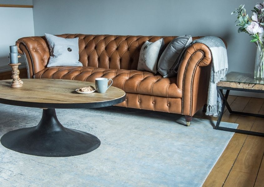 Brown leather chesterfield sofa against blue wall with oval coffee table on light blue rug