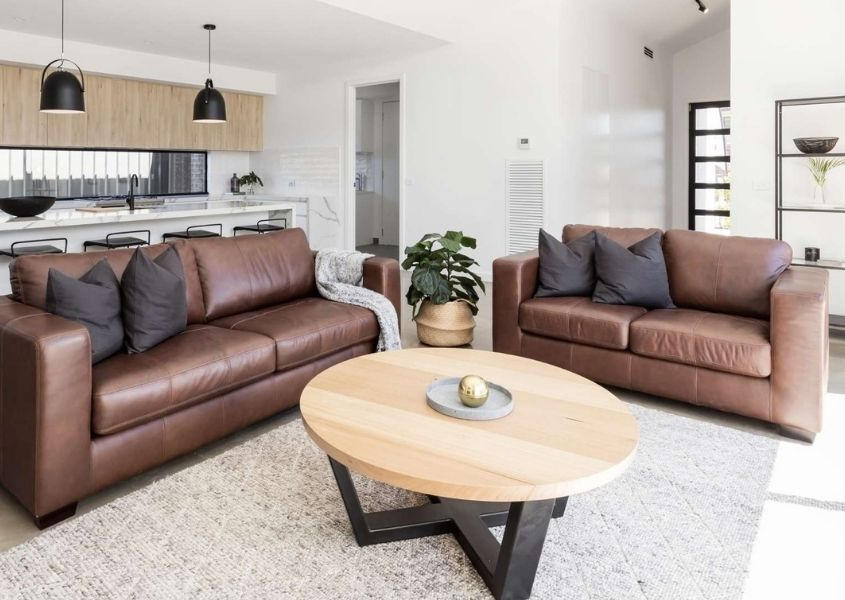 Two brown leather sofas with round industrial coffee table and black hanging pendant lights