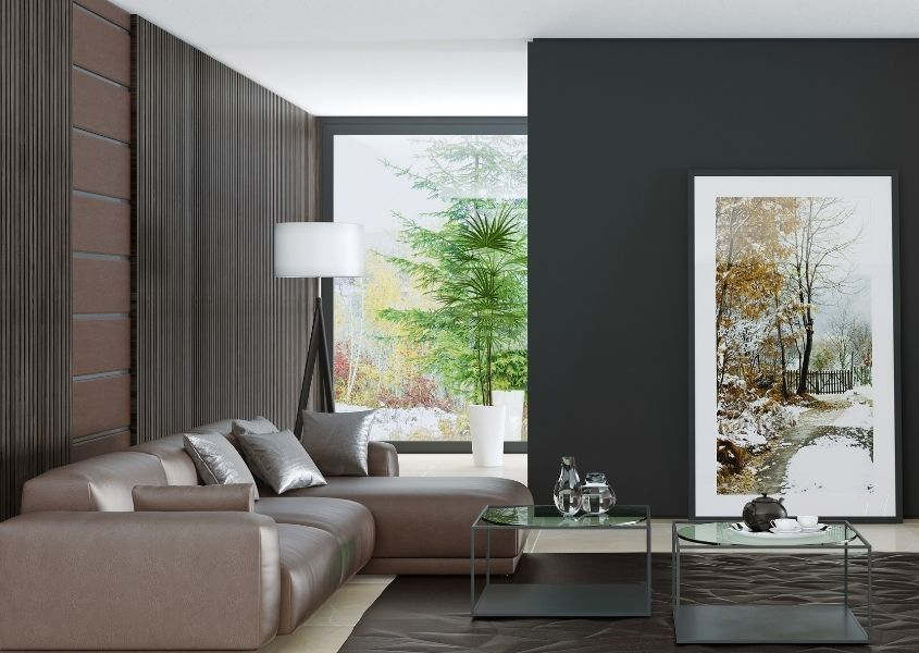 Modern brown leather sofa in large room with black walls and oversized artwork on wall
