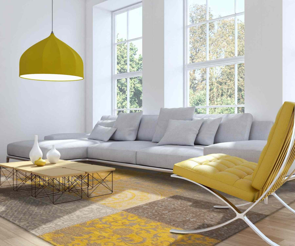 Living room with white sofa and yellow coloured pendant light, rug and armchair