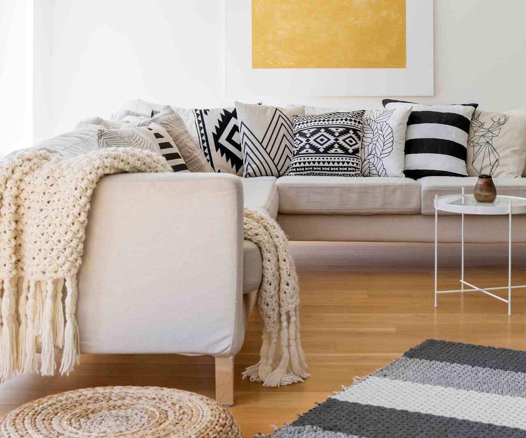 Cream modern sofa with white chunky knit throw and black and white cushions