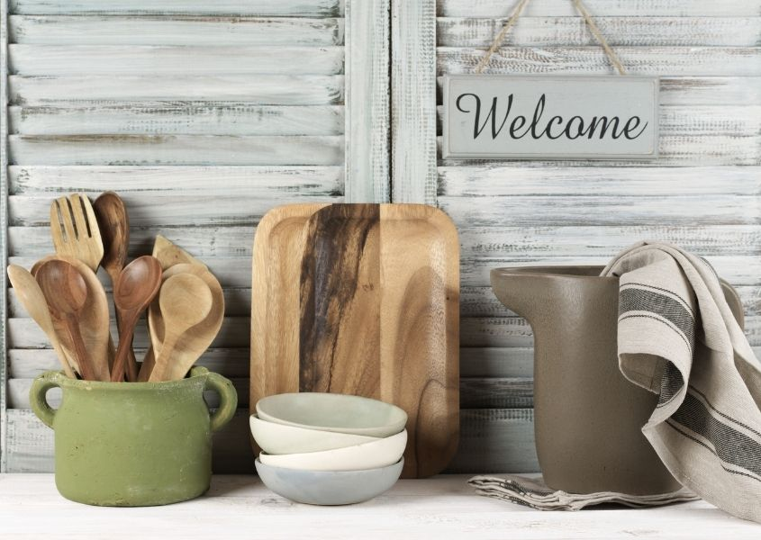 Whitewashed wooden shutters with welcome hanging sign and kitchen wooden utensils