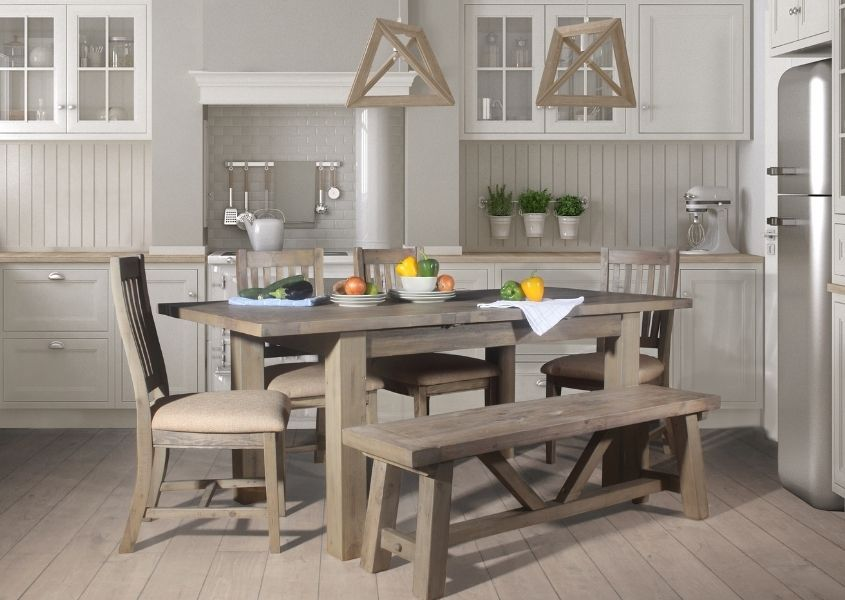 Farmhouse wooden dining table with wooden chairs in traditional kitchen