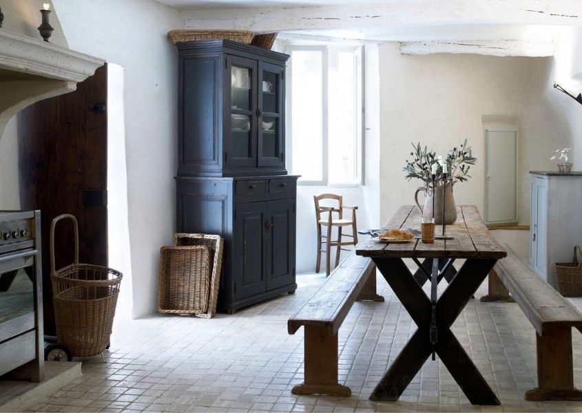 Farmhouse kitchen with large fireplace, long and thin rustic dining table and blue painted dresser