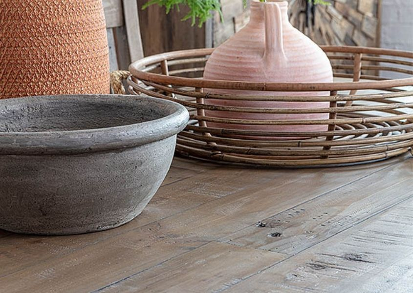 Close up of reclaimed wood dining table with terracotta and earthenware vases