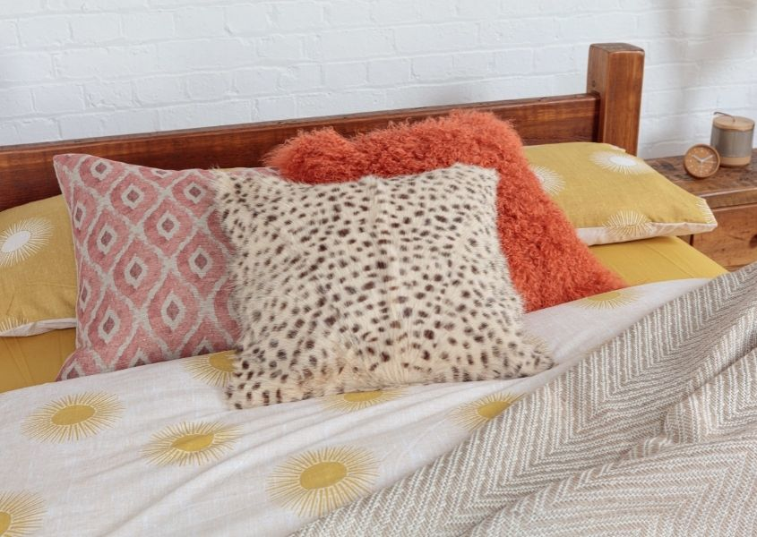 Orange, yellow and animal print cushions on wooden bed