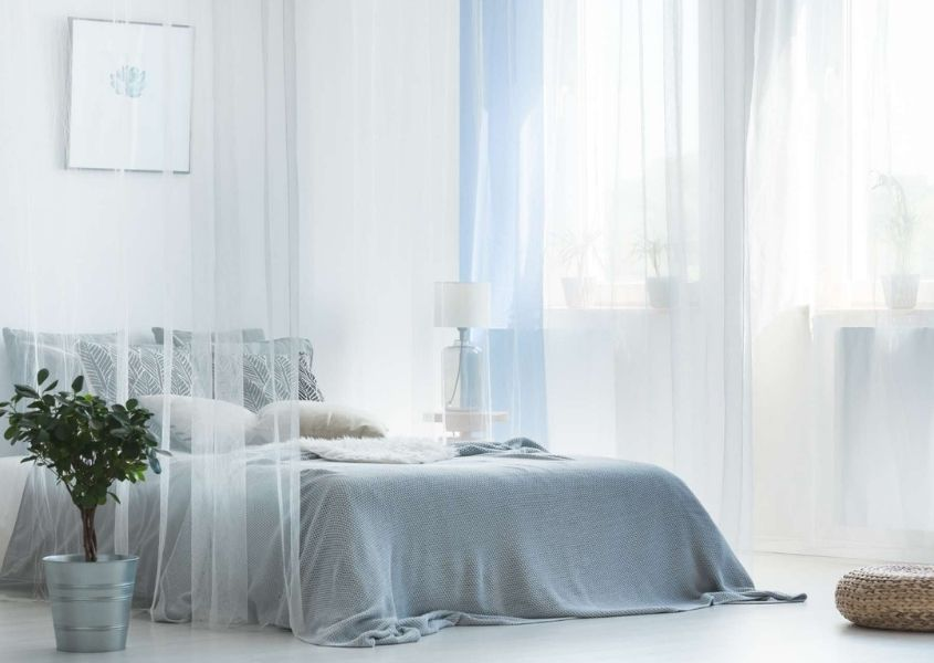 Grey double bed with sheer white curtains