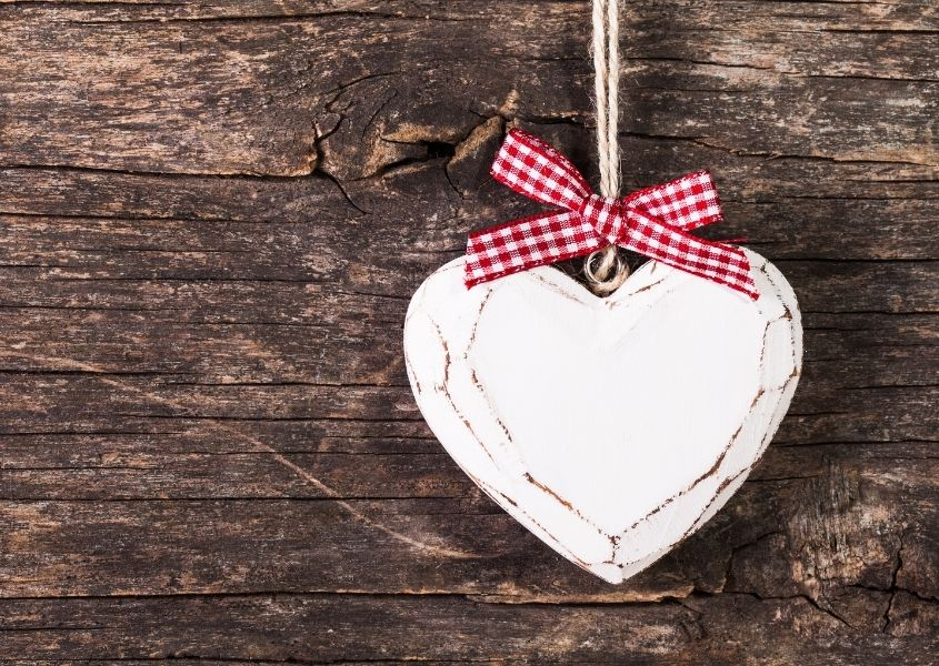 White wooden heart with red bow on rustic wood